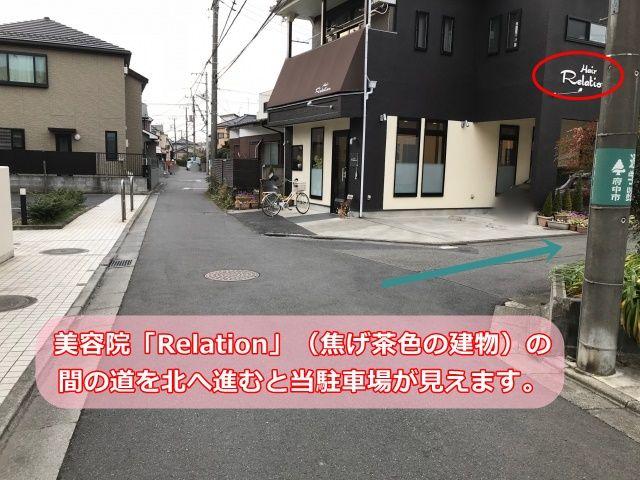 美容院「Relation」(焦げ茶色の建物)の間の道を北へ進むと当駐車場が見えます。