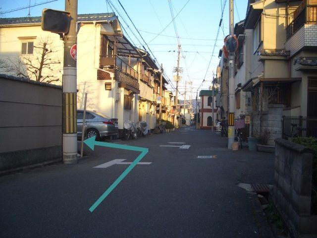 こちらの道路を矢印の方向に曲がってください。