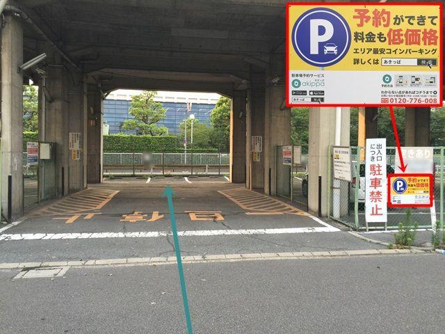 【道順5】駐車場出入口の写真です。左側のフェンスに「akippaの看板」がありますので、ご確認のうえ駐車場内へお進みください。