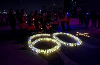 """Activists of the Red Cross NGO light up sparkling sticks forming the number """"60"""", during the """"Earth Hour"""" event at Skopje main square, on March 24, 2018.  Thousands of cities around the world turned off lights emblematic buildings during the """"Earth Hour"""", a global event to warn of the dangers of climate change. / AFP PHOTO / Robert ATANASOVSKI"""