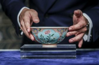 Nicolas Chow, deputy chairman for Sotheby's Asia, holds an extremely rare Qing Dynasty bowl -- one of only three known to exist -- during a media preview at Sotheby's in Hong Kong on April 3, 2018. An extremely rare Qing Dynasty bowl made for the Chinese emperor Kangxi fetched 30.4 million USD, Sotheby's said. / AFP PHOTO / ISAAC LAWRENCE
