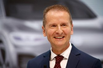 """Newly appointed CEO of German car maker Volkswagen (VW) Herbert Diess smiles as he gives a press conference at the company's headquarters in Wolfsburg, central Germany, on April 13, 2018, one day after the company announced a wider management shake-up. German auto giant Volkswagen on Thursday (April 12, 2018) had named Herbert Diess as its new chief executive, replacing Matthias Mueller, as the one-time paragon of German industry seeks to turn the page on the """"dieselgate"""" emissions scandal that has dogged it since 2015. / AFP PHOTO / Odd ANDERSEN"""