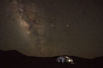 In this picture taken on July 27, 2016, a Tibetan nomad herders tent (bottom R) rests in Yushu county in the mountains of Qinghai province as the Milkyway rises in the night sky. The number of Tibetans maintaining the pastoral lifestyle is dwindling, mostly due to a Chinese government push to decrease the Tibetan nomad population and move them into resettlement villages, sometimes by force. / AFP PHOTO / NICOLAS ASFOURI