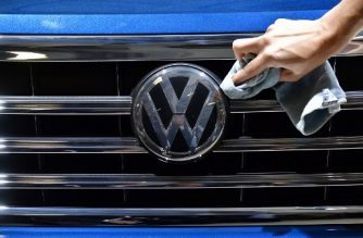 A staff member cleans the logo of a SUV VW Touareg on display ahead of the annual general meeting of German carmaker Volkswagen, in Berlin on May 3, 2018. / AFP PHOTO / Tobias SCHWARZ