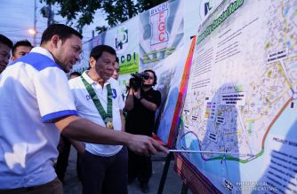 President Rodrigo Roa Duterte listens to the briefing on the Davao City Coastal Road project of Public Works and Highways Secretary Mark Villar on the sidelines of the inauguration of the Davao River Bridge widening project at Carlos P. Garcia Highway in Davao City on May 24, 2018. JOEY DALUMPINES/PRESIDENTIAL PHOTO