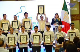 "Iglesia Ni Cristo (Church Of Christ) General Auditor Brother Glicerio Santos Jr., raises the official validated Guinness certificate for the ""largest charity walk in multiple venues"" that was announced and awarded by Guinness adjudicator Paulina Sapinska on Tuesday, June 12, 2018, during a ceremony held inside the INC Central Office in Quezon City, Philippines. (Photo by Jojo Camillo, Eagle News Service)"
