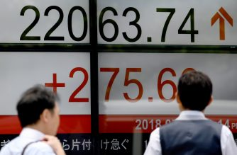 Pedestrians walk past an indicator for the numbers on the Tokyo Stock Exchange at a securities company in Tokyo on July 9, 2018.  Tokyo stocks opened higher on July 9, extending rallies in New York with the cheaper yen also supporting the market. / AFP PHOTO / Toshifumi KITAMURA