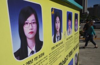 (File photo) Pedestrians walk past portraits of Cho Eun-Hwa (L), one of four students who went missing in the 2014 South Korea's Sewol ferry disaster, and other missing passengers near a memorial altar set up for the victims in Seoul on May 25, 2017. Choi's remains were confirmed through DNA test, a third victim to have been identified following the recovery of the sunken Sewol ferry, officials said.   / AFP PHOTO / JUNG Yeon-Je