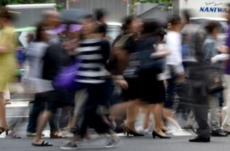 Pedestrians cross a street in Tokyo on May 31, 2017. Japanese employers are scrambling to find staff, unemployment is at its lowest level in more than two decades and the labour market is tighter than it was during Japan's booming bubble economy years. / AFP PHOTO / Toru YAMANAKA / TO GO WITH AFP STORY JAPAN-ECONOMY-UNEMPLOYMENT,FOCUS BY ANNE BEADE