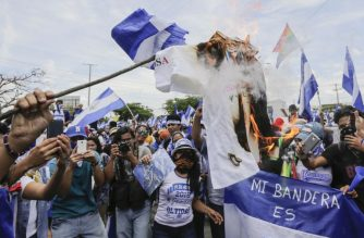 Anti-government protesters burn a government's campaign jersey, during a demonstration demanding the release of political prisoners, in Managua, on August 15, 2018. / AFP Photo / Inti Ocon