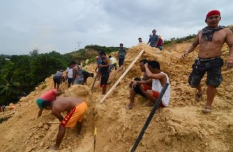 Residents dig amongst the rubble as they help rescuers search for survivors at the landslide site in Naga City, on the popular tourist island of Cebu on September 20, 2018. At least three people were killed and 10 homes buried early on September 20 in the central Philippines when heavy monsoon rains unleashed a landslide in a rural farming community, authorities said. / AFP PHOTO / ALAN TANGCAWAN