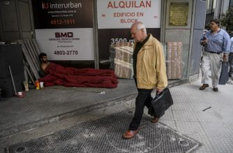People walk past a homeless man, in the financial district of Buenos Aires, on September 26, 2018. A crisis of confidence beginning in April saw the value of the peso plunge, with Argentina negotiating its $50 billion bailout loan from the IMF. The central bank hiked interest rates to a world-high 60 percent and the peso has remained largely stable since its sudden crash in August. / AFP PHOTO / EITAN ABRAMOVICH