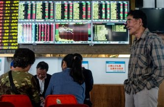 An investor looks at an electronic board showing stock information at a brokerage house in Shanghai on October 15, 2018. - Asian stocks started the week on the back foot on October 15, with investors still in gloomy mood after several days of market turbulence sparked by trade rows and a spat over the US central bank. (Photo by Johannes EISELE / AFP)