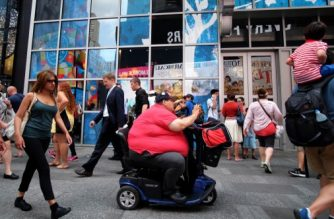 A man on an electric scooter makes his way with other pedestrians in New York on July 1, 2015. AFP PHOTO/JEWEL SAMAD (Photo by JEWEL SAMAD / AFP)
