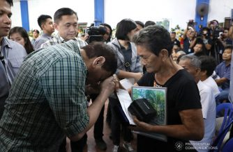 President Rodrigo Roa Duterte shows a gesture of respect to the relative of one of the slain police officers during his visit at the Camarines Sur Provincial Police Office in Naga City on October 23, 2018. SIMEON CELI JR./PRESIDENTIAL PHOTO