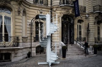 A man looks at section of stairs from the Eiffel Tower's original structure displayed outside the Artcurial French auction house ahead of its forthcoming sale in Paris on November 8, 2018. (Photo by Philippe LOPEZ / AFP)