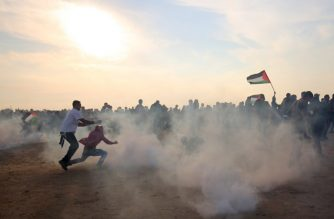 Palestinians run for cover from tear gas during clashes near the border between Israel and Khan Yunis in the southern Gaza Strip on November 9, 2018. (Photo by SAID KHATIB / AFP)