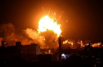 """A picture taken on November 12, 2018 shows a ball of fire above the building housing the Hamas-run television station al-Aqsa TV in Gaza City during an Israeli air strike. - Israel's military said it was carrying out air strikes """"throughout the Gaza Strip"""" after rocket fire from the Palestinian enclave towards its territory. (Photo by Bashar TALEB / AFP)"""