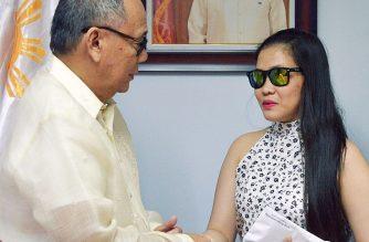 Foreign Affairs Undersecretary Ernesto Abella hands over the P100,000 financial assistance to Jennifer Dalquez. /DFA/
