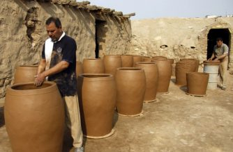 Iraqis making clay pots in Najaf on November 11, 2018. - Pottery has deep roots in Iraq, where ancient civilisations turned to clay to build their homes, shape their cooking utensils, and even make their ovens. (Photo by Haidar HAMDANI / AFP)