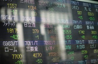 A picture taken in Tokyo on November 21, 2018 shows a stock indicator board showing the share prices of Japanese companies, with Nissan shares in the middle. (Photo by Martin BUREAU / AFP)