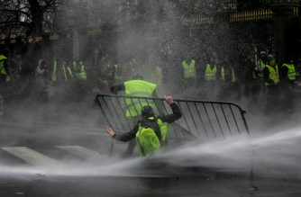"""Anti-riot police use a water cannon during clashes with """"yellow vest"""" (Gilet Jaune) protesters during a demonstration on November 30, 2018, near major EU buildings in Brussels. - Around 300 people demonstrated at the call of the spreading """"yellow vest"""" movement, which had already organised large protests across France to complain about fuel tax increases. (Photo by Aris Oikonomou / AFP)"""