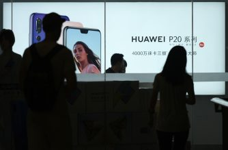 (FILES) This file photo taken on August 6, 2018 shows people walking past a Huawei store in Beijing. - China reacted furiously on December 6 after a top executive and daughter of the founder of Chinese telecom giant Huawei was arrested in Canada following a US extradition request, threatening to rattle a trade war truce with the United States. (Photo by WANG Zhao / AFP)