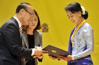 """(FILES) This file photo taken on January 31, 2013 shows Myanmar's Aung San Suu Kyi (R) receiving the Gwangju Prize for Human Rights in the southwestern city of Gwangju. - One of South Korean largest human rights groups will strip Myanmar's de facto leader Aung San Suu Kyi of its 2004 prize because of her """"indifference"""" to the atrocities against the Rohingya minority, organisers said on December 18, 2018. (Photo by Jung Yeon-je / AFP)"""