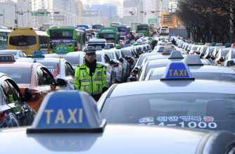 A policeman walks among South Korean taxis taking part in a one-day strike during a rally calling for the car-pooling app to be banned, near the National Assembly in Seoul on December 20, 2018. - Tens of thousands of taxi drivers in South Korea went on a nationwide strike on December 20, snarling up traffic in Seoul, in the latest protest at a planned Uber-like ride-sharing service. (Photo by Jung Yeon-je / AFP)