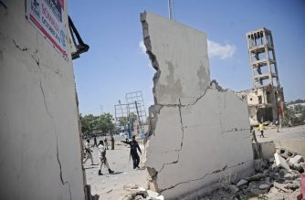 People stand next to destroyed walls at the scene of a car bombing attack in Mogadishu, Somalia, on December 22,2018. - Seven people were killed  in a double car bomb attack claimed by the jihadist Shabaab group near the presidential palace in the Somali capital Mogadishu, police said. (Photo by Mohamed ABDIWAHAB / AFP)