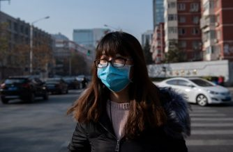 A woman wears a mask to fight bad air pollution in Beijing on November 30, 2018. (Photo by Nicolas ASFOURI / AFP)