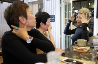 "This photo taken on December 26, 2018 shows 56-year-old Chinese model Ma Yinhong (R) talking to her friends at a cafe in central Shanghai. - Wearing a bright floral ensemble with her short hair dyed blonde, Chinese model Ma Yinhong struts a Shanghai catwalk with a style and swagger that belie her 56 years. Ma is one of a growing number of older models sought after by Chinese and international labels trying to court the country's growing faction of ""silver spenders"". (Photo by Matthew Knight / AFP) / TO GO WITH AFP STORY FASHION-LIFESTYLE-CHINA-ELDERLY,FEATURE BY LIANCHAO LAN"