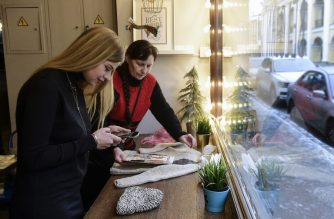 "Nina Lozhkova, 58, a participant of Granny's Instagram project, presents her knits to the founder of the project, Yulia Aliyeva, 27, in Saint Petersburg on December 21, 2018. - Elderly women across Russia are often seen selling their hand-knitted wares on pavement corners for a few rubles to supplement meagre pensions. Now a new Instagram project aims to change the public perception of their homely skills by promoting ""granny chic"" and help the women sell their knitted mittens, socks and other items online. (Photo by Olga MALTSEVA / AFP)"