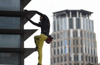 "French urban free-climber Alain Robert, popularly known as the ""French Spiderman,"" is pictured on the side of the 47-storey GT Tower in the Philippines' financial district of Makati on January 29, 2019. The 56-year-old adventurer climbed the 47-storey GT Tower without safety equipment, leaving watchers on the ground staring agape. (Ted Aljibe/ AFP)"