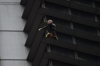 "French urban free-climber Alain Robert, popularly known as the ""French Spiderman"", is pictured on the side of the 47-storey GT Tower in Manila's financial district of Makati on January 29, 2019. - The 56-year old adventurer climbed the 47-storey GT Tower without safety equipment, leaving watchers on the ground staring agape. (Photo by TED ALJIBE / AFP)"