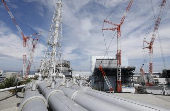 In this picture taken on July 27, 2018 and made available on July 30, 2018, pipes for ground water bypass are arranged above the reactor unit 1 (L), unit 2 (C) and partially unit 3 of the tsunami-crippled Tokyo Electric Power Company (TEPCO) Fukushima Dai-ichi nuclear power plant in Okuma, Fukushima prefecture. - The Fukushima nuclear disaster was triggered by a massive earthquake and ensuing tsunami in March 2011, which wrecked cooling systems at the plant on Japan's northeast coast, sparking reactor meltdowns and radiation leaks. (Photo by Kimimasa MAYAMA / POOL / AFP)