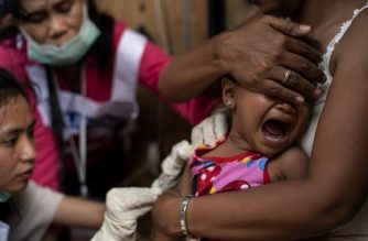 A child reacts during a Philippine Read Cross Measles Outbreak Vaccination Response in Baseco compound, a slum area in Manila on February 16, 2019. - A growing measles outbreak in the Philippines killed at least 25 people last month, officials said, putting some of the blame on mistrust stoked by a scare over an anti-dengue fever vaccine. (Photo by Noel CELIS / AFP)