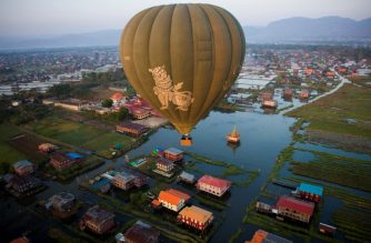This aerial photo taken from a hot air balloon shows a hot air balloon flying over traditional houses on stilts on Inle lake in Shan State on February 18, 2019. - Myanmar's famed Inle Lake has enchanted tourists for decades with its floating gardens and the graceful leg-rowing style of its fisherman, but experts warn the lake is drying up and urgent action is needed to avoid disaster. (Photo by Ye Aung THU / AFP)