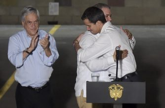 """Venezuela's opposition leader Juan Guaido (R) and President Ivan Duque (C) embrace each other as Chilean President Sebastian Pinera applauds, during a press conference after attending the """"Venezuela Aid Live"""" concert, organized to raise money for the Venezuelan relief effort, in Cucuta, Colombia, on February 22, 2019. - Guaido -- recognized by more than 50 countries as interim president -- attended the aid concert in Colombia despite having been barred from leaving the country by the government of rival Nicolas Maduro. (Photo by Raul ARBOLEDA / AFP)"""
