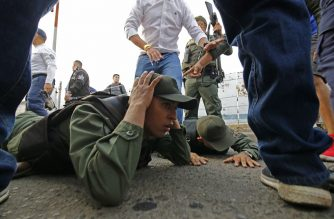 Two Venezuelan soldiers lie on the ground as they are detained by Colombian police after driving into Colombia in an armor car from the Venezuelan side of Simon Bolivar International bridge in Cucuta on February 23, 2019. - According to Colombian authorities four soldiers of the Venezuelan guard deserted this Saturday after crossing two border bridges with Colombia, closed by order of the government of Nicolás Maduro before the announcement of the entry of aid shipments. Three of the soldiers were mobilized in a white tank and knocked down one of the security fences of the Simón Bolívar Bridge, in the Colombian city of Cúcuta, said a Colombian Immigration officer (Photo by Schneyder Mendoza / AFP)