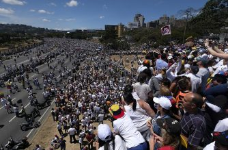 Supporters of Venezuelan opposition leader Juan Guaido take part in a rally in Caracas, on February 23, 2019. - Venezuela braced for a showdown between the military and regime opponents at the Colombian border on Saturday, when self-declared acting president Juan Guaido has vowed humanitarian aid would enter his country despite a blockade. (Photo by Matias Delacroix / AFP)