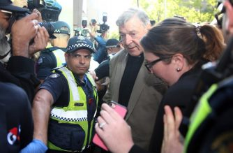 A police officer (L) clears the way for Cardinal George Pell as he arrive at court in Melbourne on February 27, 2019. - Cardinal George Pell arrived in court, possibly for the last time as a free man, in a last-ditch push to apply for bail after his historic conviction for child sex crimes. (Photo by Con CHRONIS / AFP)
