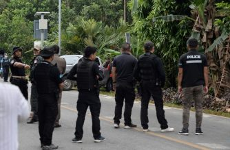Police secure the area as authorities recover the bodies of a Buddhist and a Muslim policemen in the restive southern Thailand province of Narathiwat on February 27, 2019. - Two Thai policemen were executed after being abducted from a tea shop in the kingdom's violent southern borderlands, police said February 27, as bloodshed again spikes in a 15-year insurgency. (Photo by Madaree TOHLALA / AFP)