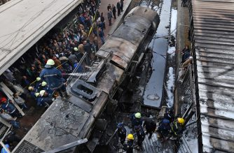 Fire fighters and onlookers gather at the scene of a fiery train crash at the Egyptian capital Cairo's main railway station on February 27, 2019. - The crash killed at least 20 people, Egyptian security and medical sources said. The accident, which sparked a major blaze at the Ramses station, also injured 40 others, the sources said. (Photo by STRINGER / AFP)