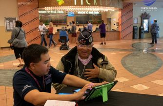 EBC's Alfred Acenas assisting William Wright in purchasing his ticket online. Photo by Des Acenas.