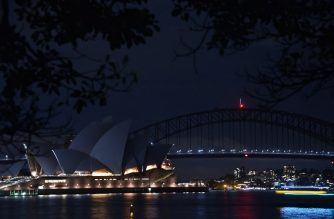 Sydney Harbour Bridge and the Opera House are plunged into darkness for the Earth Hour environmental campaign on March 24, 2018. - The lights went out on two of Sydney's most famous landmarks for the 11th anniversary of the climate change awareness campaign Earth Hour, among the first landmarks around the world to dim their lights for the event. (Photo by PETER PARKS / AFP)