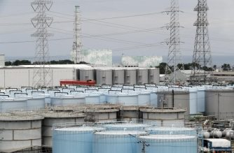 This picture taken on July 27, 2018 and made available on July 30, 2018 shows reactor unit 5 (L) and 6 over storage tanks of radiation contaminated water at the tsunami-crippled Tokyo Electric Power Company (TEPCO) Fukushima Dai-ichi nuclear power plant in Okuma, Fukushima prefecture. - The Fukushima nuclear disaster was triggered by a massive earthquake and ensuing tsunami in March 2011, which wrecked cooling systems at the plant on Japan's northeast coast, sparking reactor meltdowns and radiation leaks. (Photo by Kimimasa MAYAMA / POOL / AFP)