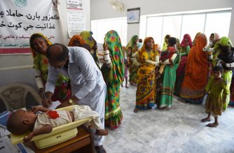 In this picture taken on May 25, 2018, a Pakistani paramedic weighs a child at Mithi Civil Hospital in Mithi, a remote town in southern Pakistan. - A frantic mother cradling her seven-month-old baby rushes towards the special paediatric ward in a desolate Pakistan town, his eyes are blank and he is smaller than most newborns. (Photo by RIZWAN TABASSUM / AFP) / To go with PAKISTAN-HEALTH-INFANTS-MALNUTRITION,FOCUS by Ashraf KHAN