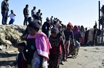 Myanmar Navy personnel escort Rohingya Muslims back to their camp in Sittwe, Rakhine state, on November 30, 2018. - Nearly 100 Rohingya Muslims were forced back to Myanmar's Rakhine state after being detained at sea en route to Malaysia, police said on November 28, stirring fears of a fresh refugee boat crisis. (Photo by - / AFP)