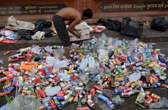 A scavenger collects discarded plastic bottles and cans outside a Buddhist temple in Phnom Penh on February 22, 2019. (Photo by TANG CHHIN Sothy / AFP)